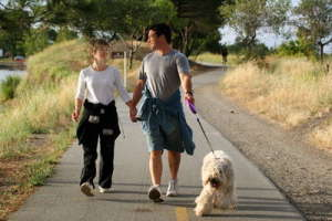 couple walking their dog in the park