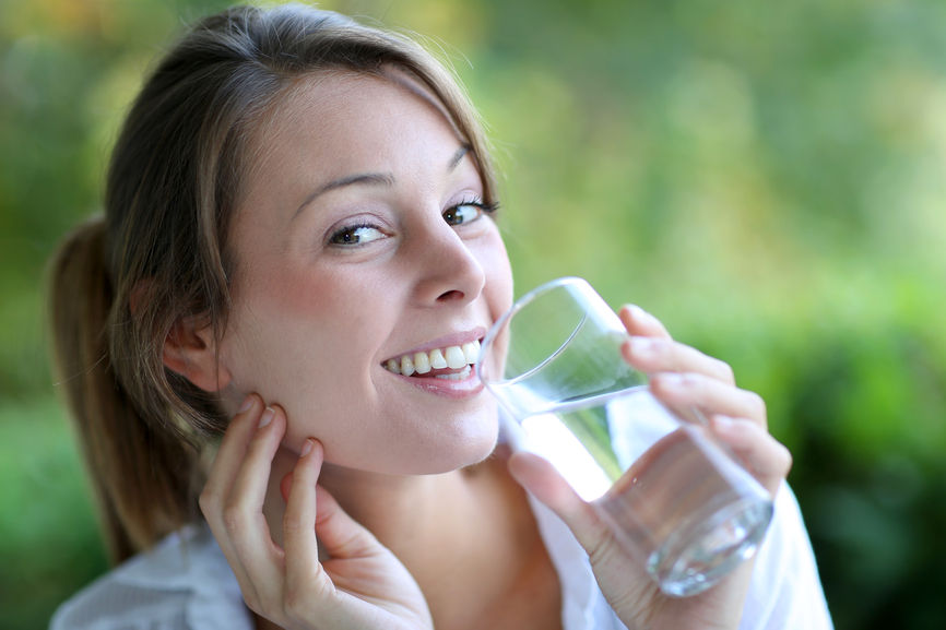 Smiling woman drinking fresh water from glass