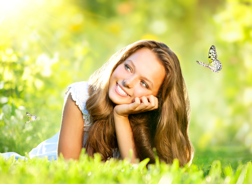Spring Beauty. Beautiful Girl Lying on Green Grass outdoor
