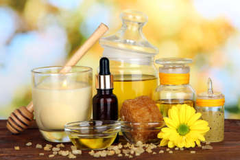Fragrant honey spa with oils and honey on wooden table on natural background