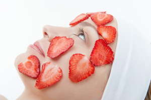 Beautiful young woman receiving facial mask of strawberry in bea