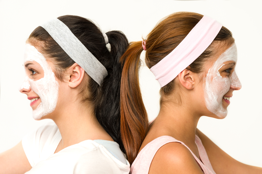 Girls sitting back-to-back wearing facial mask