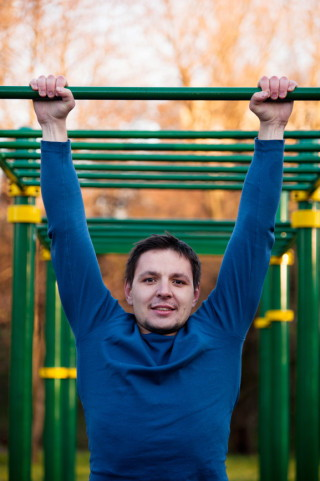 Athletic man doing pull-up on horizontal bar