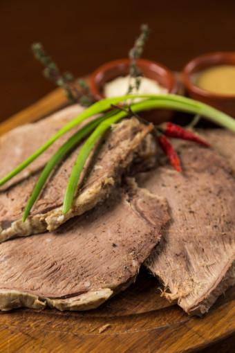sliced boiled meat presentation on wood board