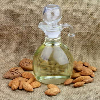 A bottle of almond oil with nuts