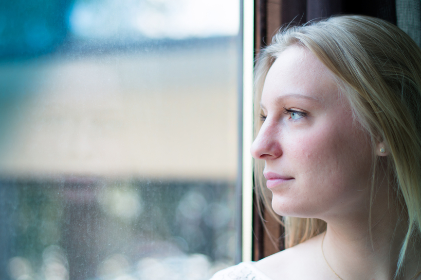 woman standing by a window looking outside
