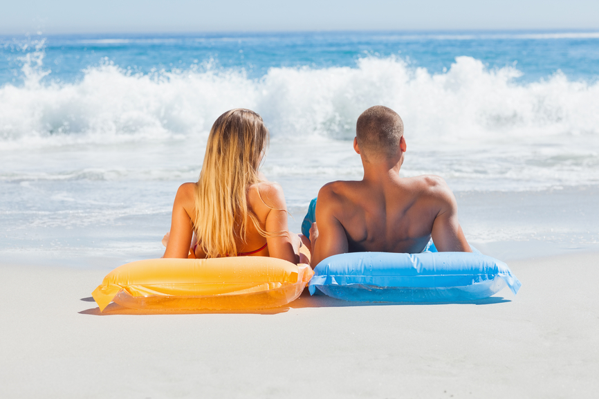 Cute couple in swimsuit sunbathing together on the beach