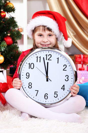 Beautiful little girl with clock in anticipation of New Year in festively decorated room