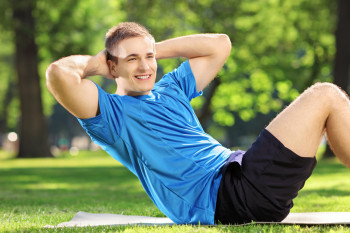 Young man athlete exercising abs in a park