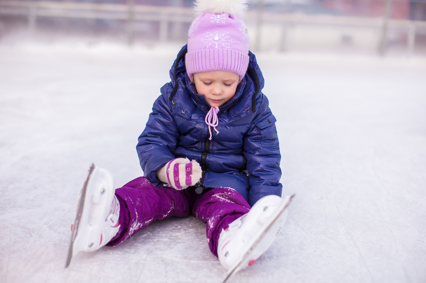 Adorable little girl sitting on ice with skates after the fall