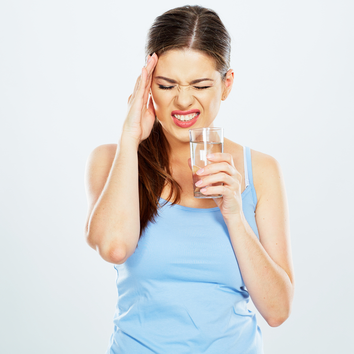 woman with headache hold water glass