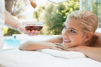 Close-up of an attractive young woman receiving spa treatment with honey