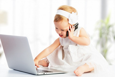 dollarphotoclub_58811166-baby-on-laptop-and-phone-700x470