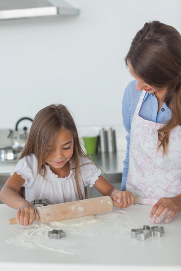 Little girl spreading a dough with a rolling spin in the kitchen