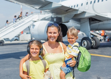 Young mother with two kids in front of airplane