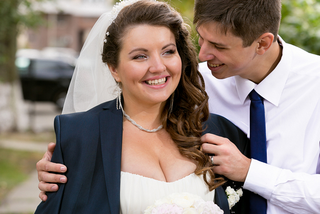 portrait of handsome groom hugging chubby bride from back