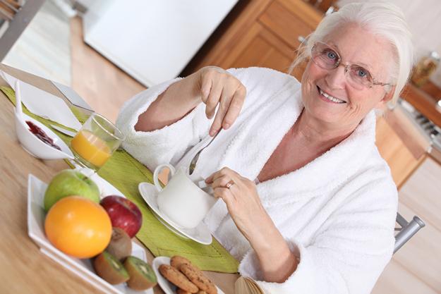 Elderly woman having breakfast