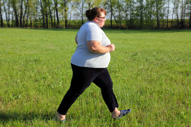 Overweight woman running on meadow