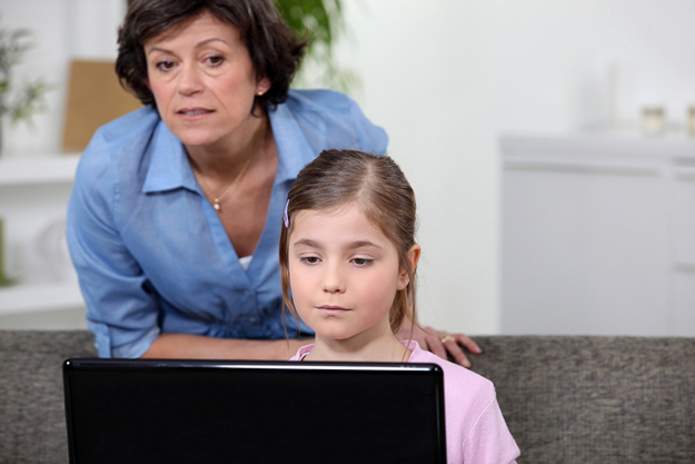 Woman and girl looking at a laptop computer